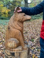 Wooden sculpture of a dog that I am petting